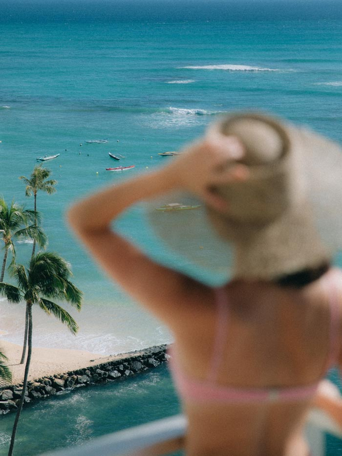 Woman in a hat looking at the beach
