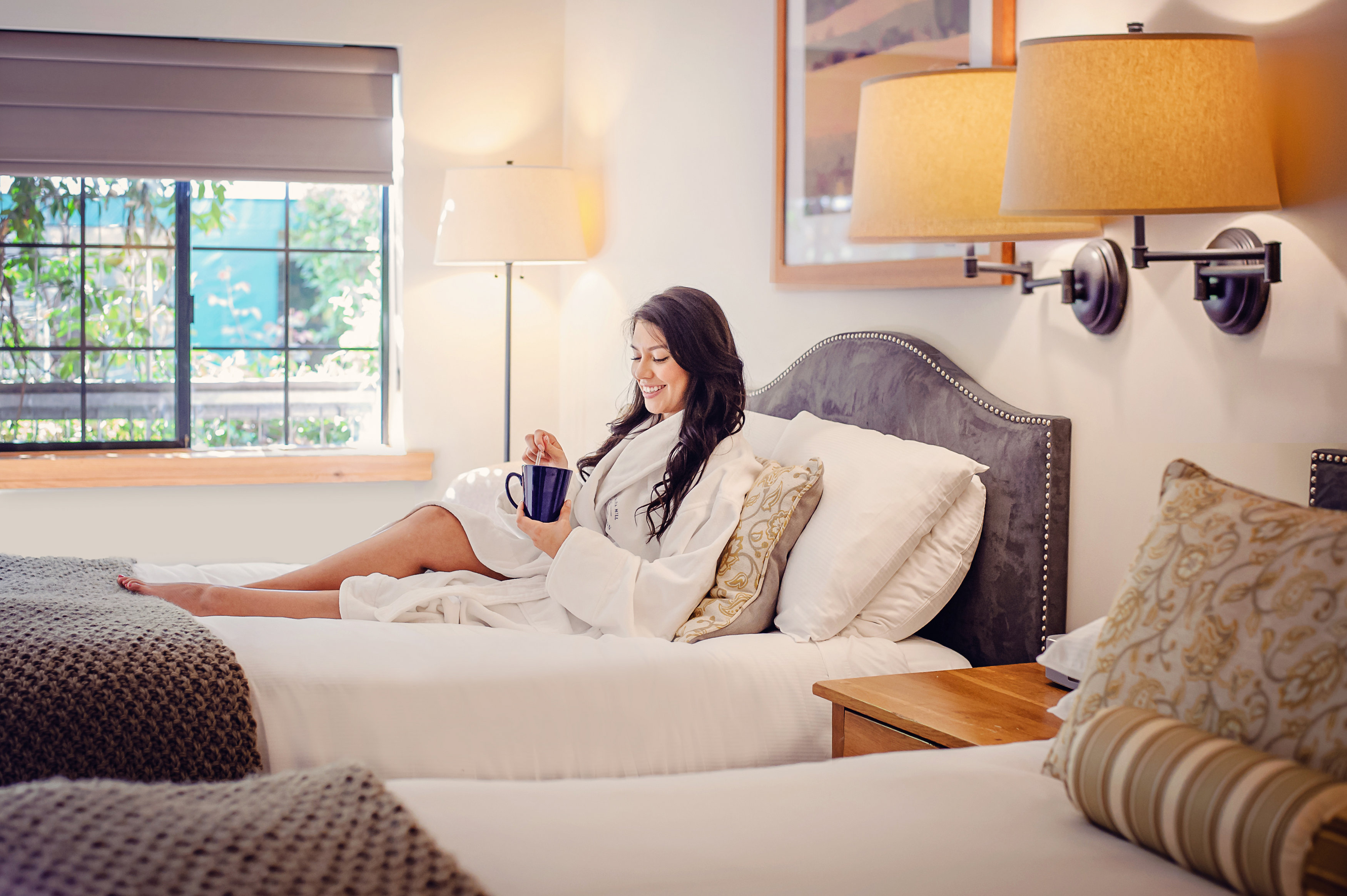 guest relaxing in bed enjoying freshly-brewed coffee